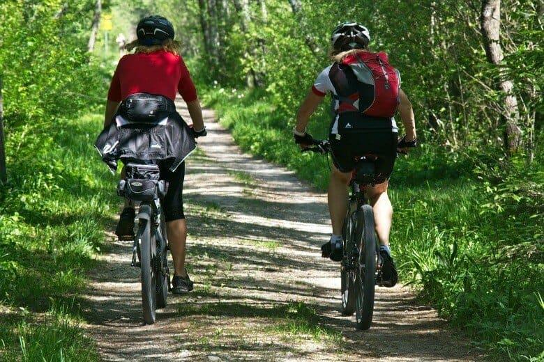 2 girls cycling down a dirt road