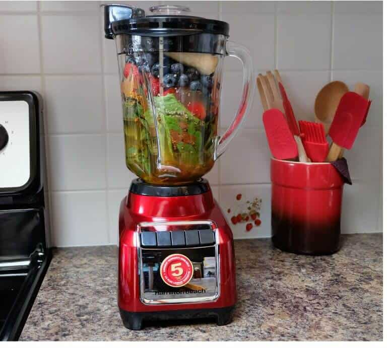 Hamilton Beach Wave-Action Blender on counter filled with fruit