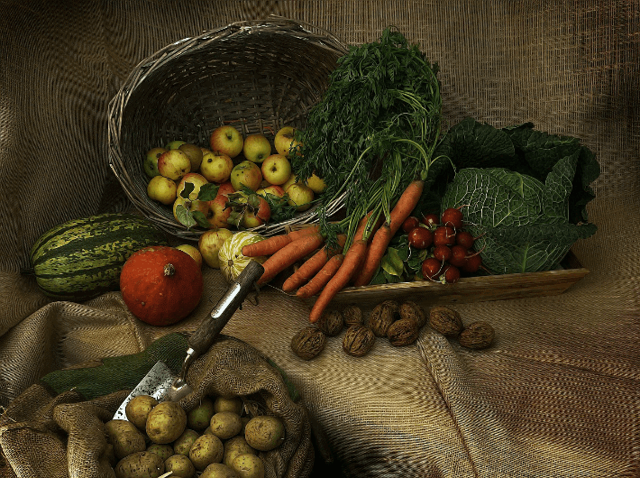 harvested vegetables and fruit in a basket on material
