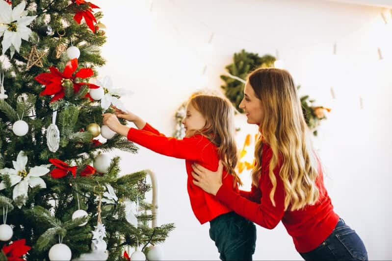 Mom and daughter decorating a Christmas tree