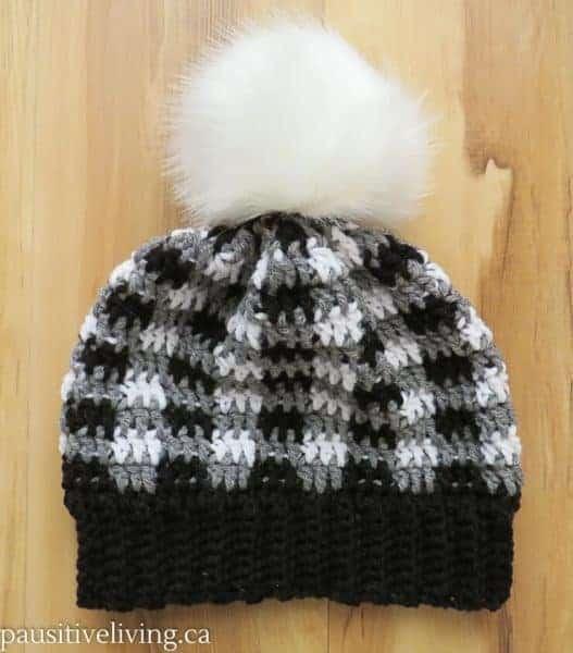 Black, grey and white plaid hat with white pom pom.