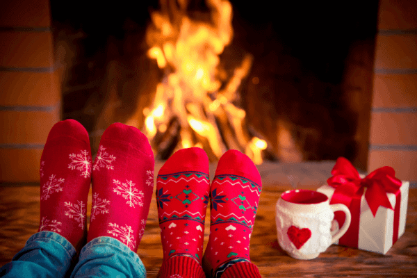 relaxing by the fireplace wearing holiday socks - depositphotos