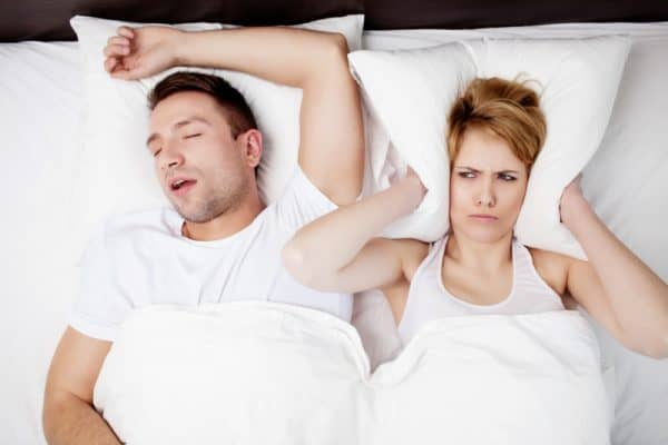 Snoring man and young woman. Couple sleeping in bed. Depositphoto